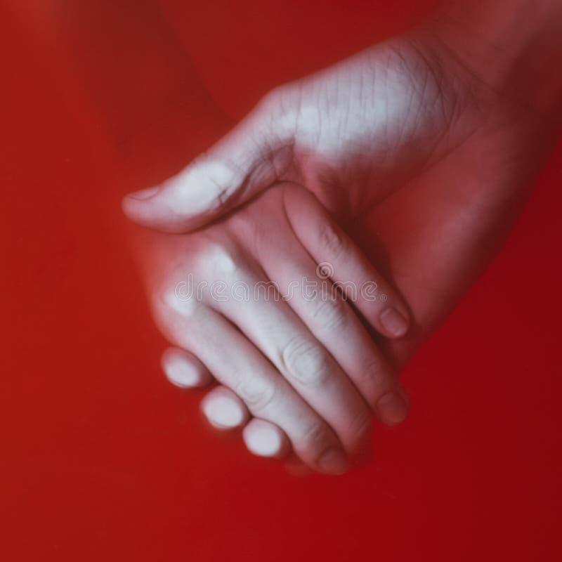 Uomo che tiene la mano di un'acqua del sangue della donna in rosso, relazione delle coppie, il concetto del prezzo di amore fotografia stock
