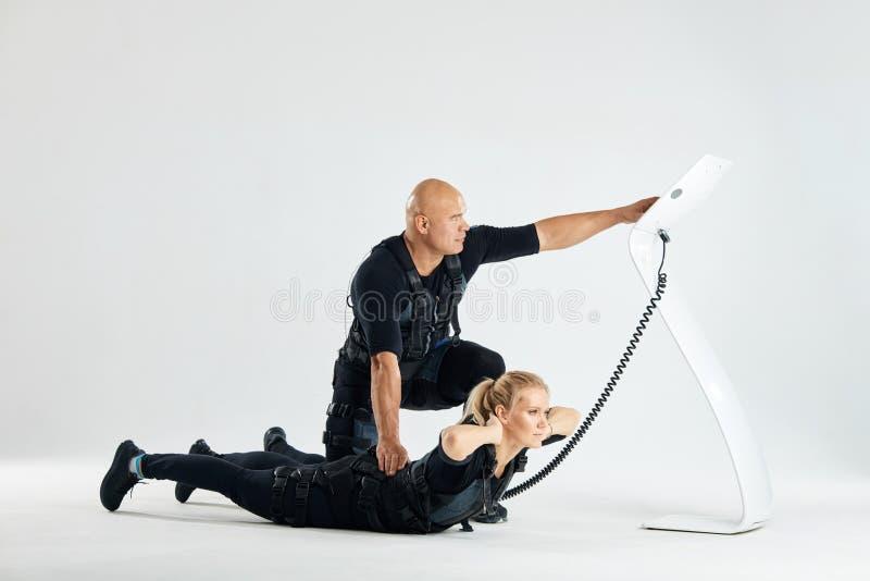Uomo che tiene la parte posteriore di una donna e che preme il bottone del dispositivo di SME fotografie stock libere da diritti