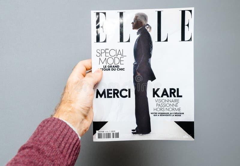 Uomo che tiene la rivista di Elle che caratterizza morte di Karl Lagerfeld della copertura fotografia stock
