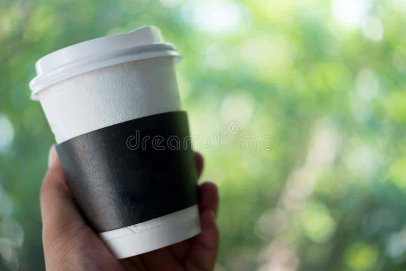 Uomo che tiene la tazza di caff? di carta asportabile con il contenitore di cartoncino immagini stock