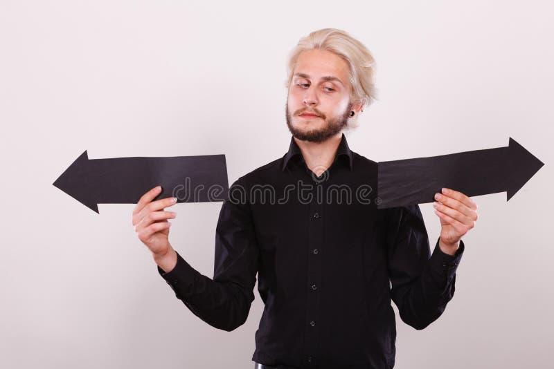 Uomo che tiene le frecce nere che indicano a destra e a sinistra immagini stock