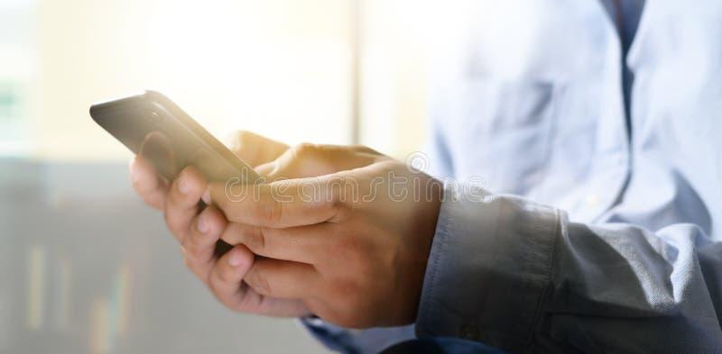 Uomo che tiene le mani dell'en e che per mezzo del telefono digitale del telefono cellulare della compressa con il ghiaione in bi fotografie stock