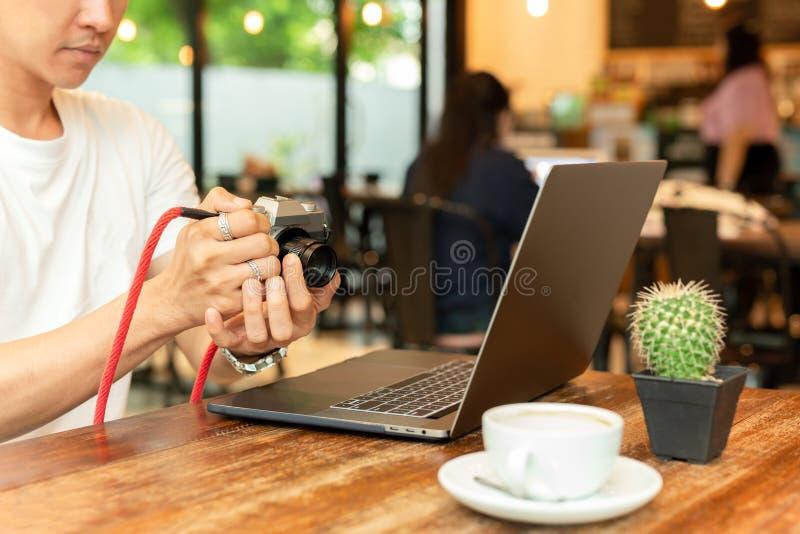 Uomo che tiene macchina fotografica mirrorless digitale che controlla foto con il computer portatile sulla tavola immagine stock