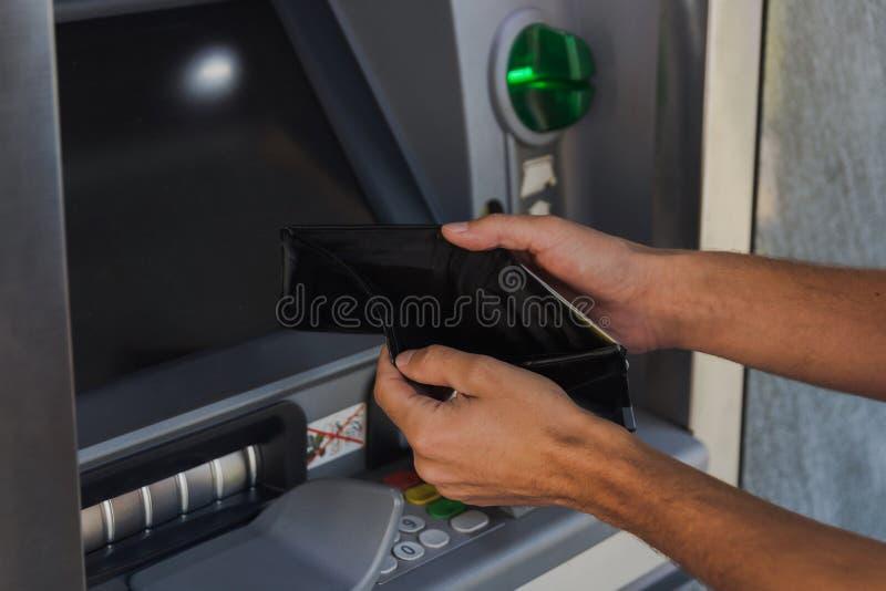 Uomo che tiene portafoglio vuoto vicino alla macchina di BANCOMAT Il concetto di essere si ? rotto fotografia stock
