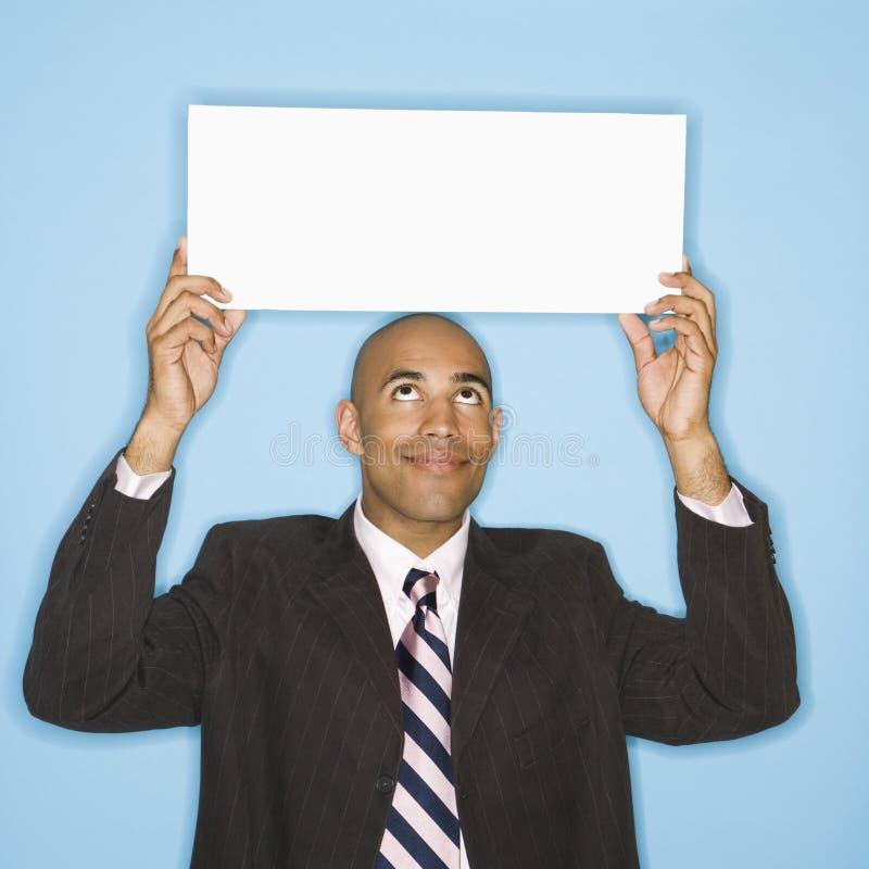 Uomo che tiene segno in bianco. immagini stock