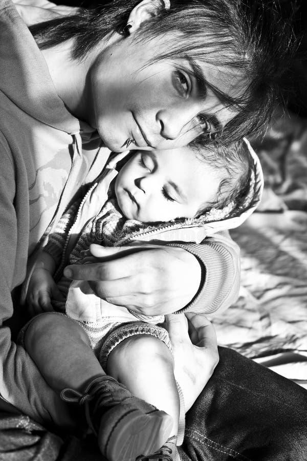 Uomo che tiene un bambino addormentato nelle sue armi immagine stock
