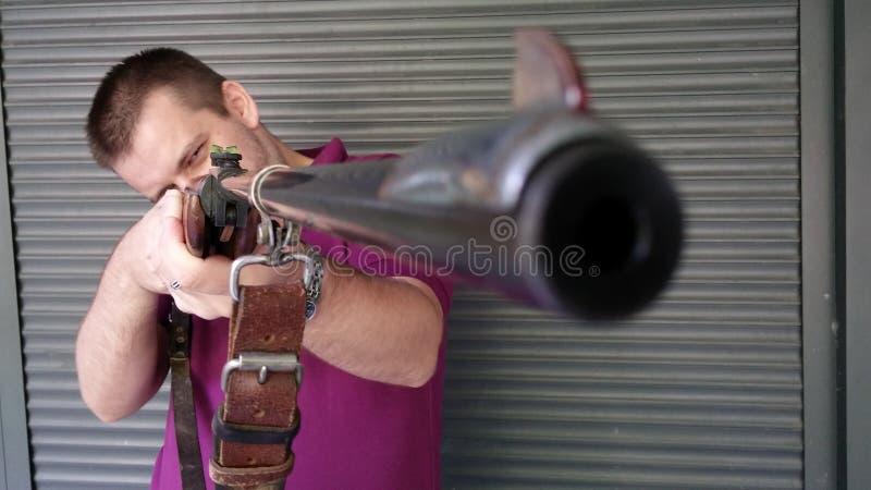 Uomo che tiene un fucile da caccia d'annata fotografia stock