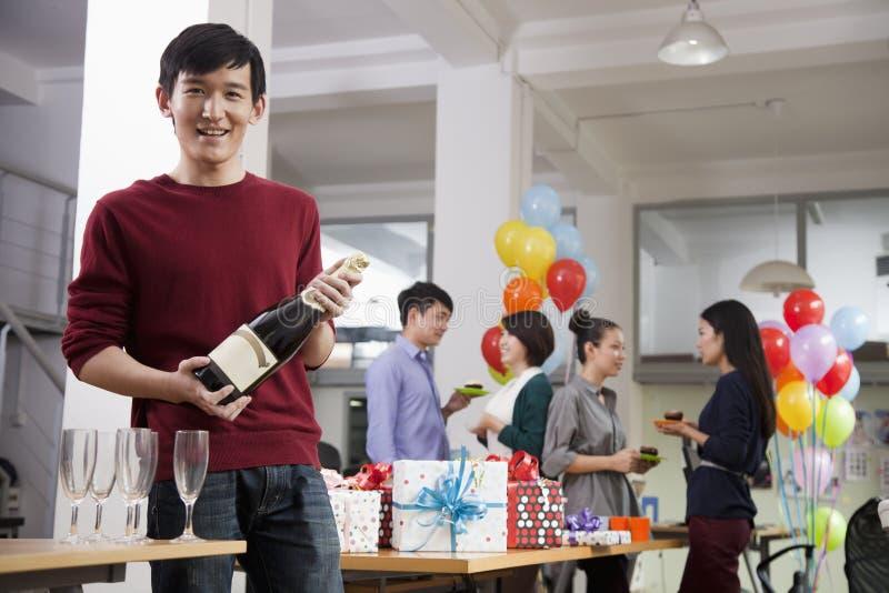 Uomo che tiene una bottiglia di Champagne At Office Party fotografia stock libera da diritti