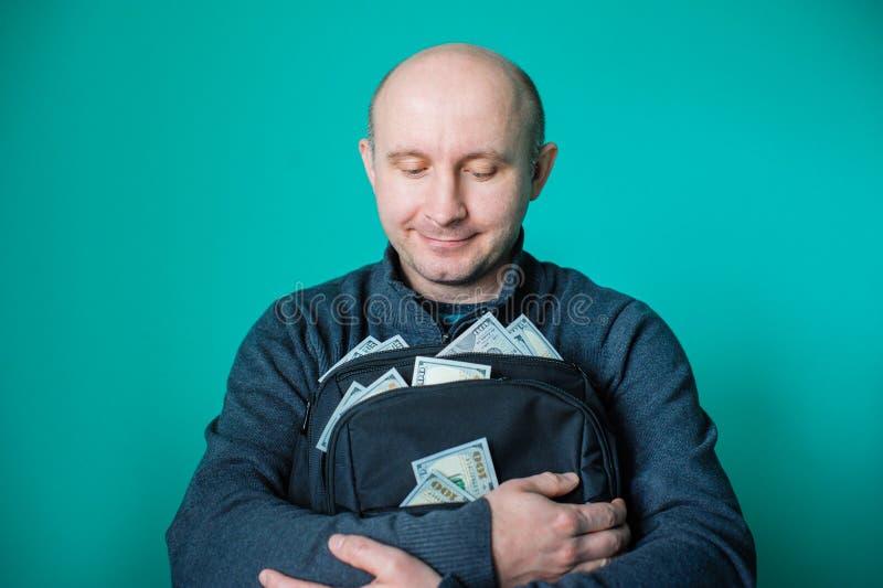 Uomo che tiene una cartella nera con i dollari immagini stock libere da diritti
