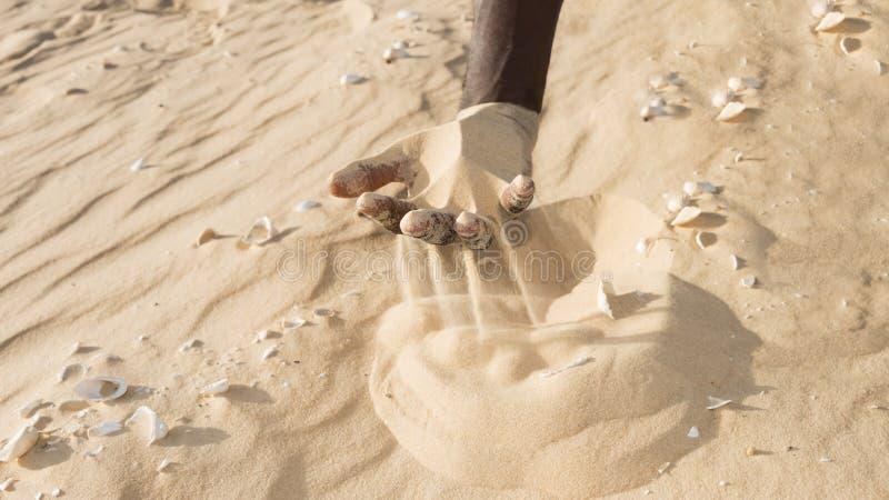 Uomo che tiene una certa sabbia nella mano fotografia stock