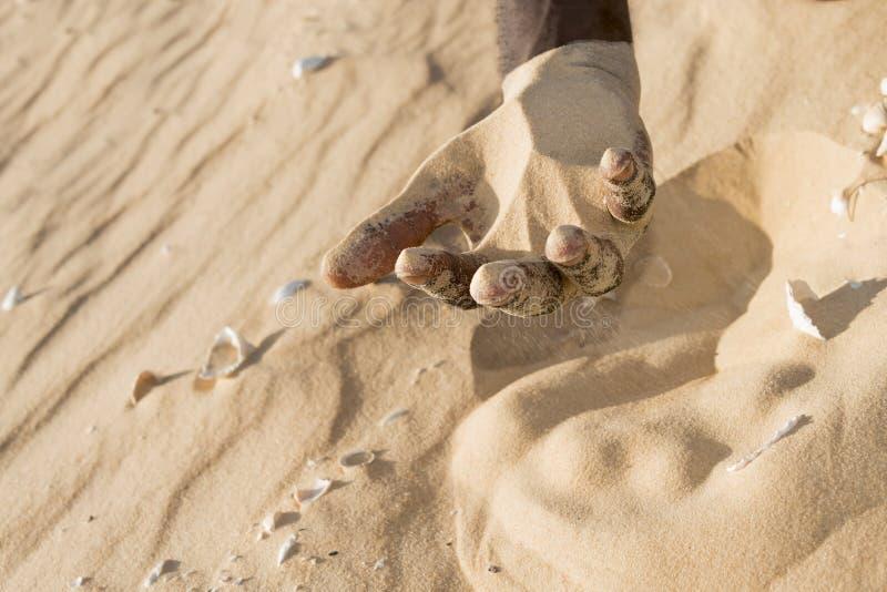 Uomo che tiene una certa sabbia nella mano fotografia stock libera da diritti