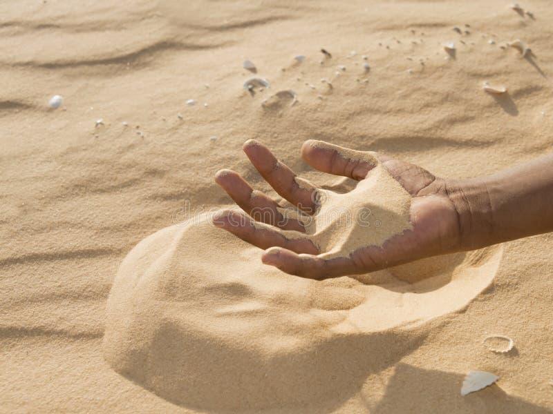Uomo che tiene una certa sabbia nella mano immagini stock libere da diritti