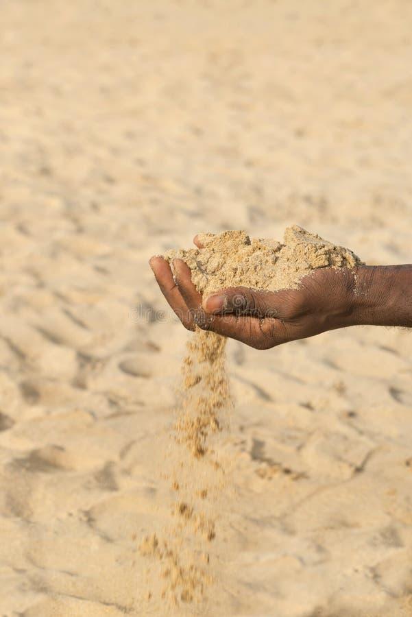 Uomo che tiene una certa sabbia nella mano: siccità e desertificazione immagine stock