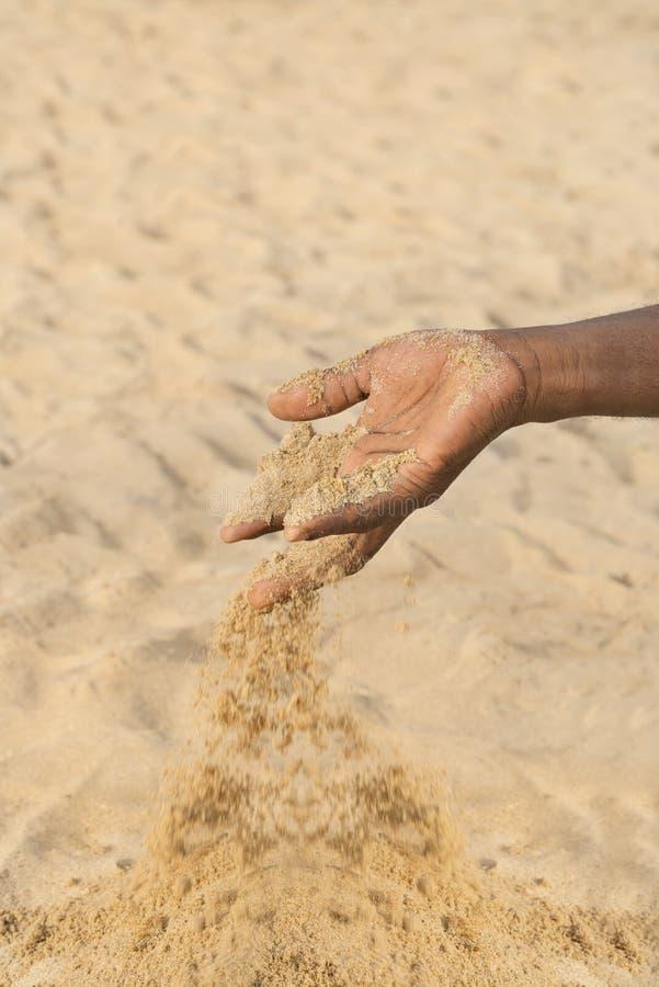 Uomo che tiene una certa sabbia nella mano: siccità e desertificazione fotografie stock