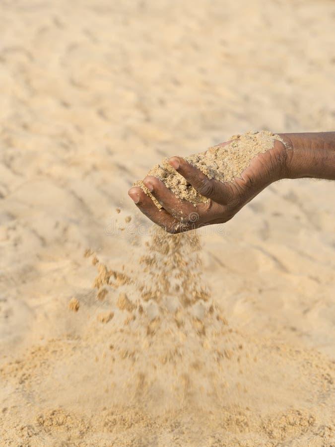 Uomo che tiene una certa sabbia nella mano: siccità e desertificazione immagine stock libera da diritti