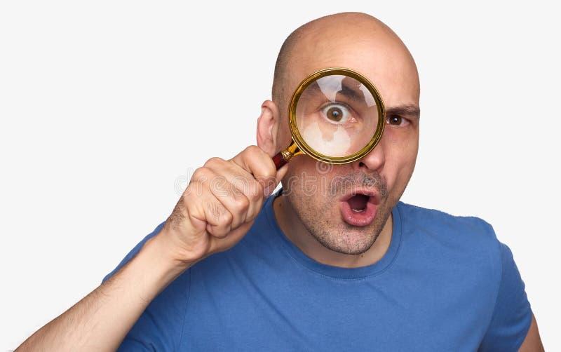 Uomo che tiene una lente d'ingrandimento fotografia stock libera da diritti