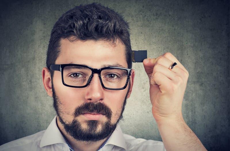 Uomo che tiene una scheda di memoria dell'unità di elaborazione dalla sua testa fotografia stock