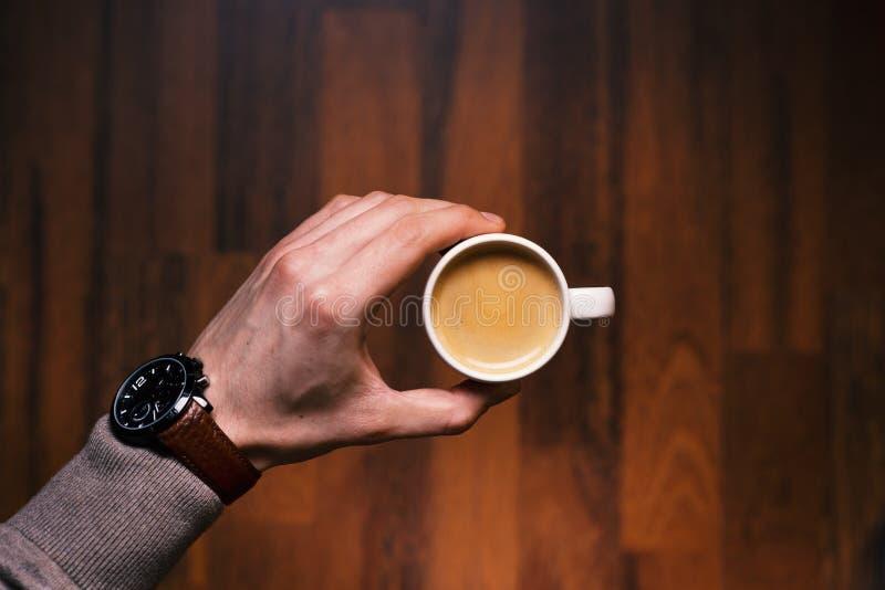 Uomo che tiene una tazza di caffè su un fondo di legno e d'annata Mano di giovane uomo d'affari che tiene una tazza di caffè Toni immagine stock libera da diritti