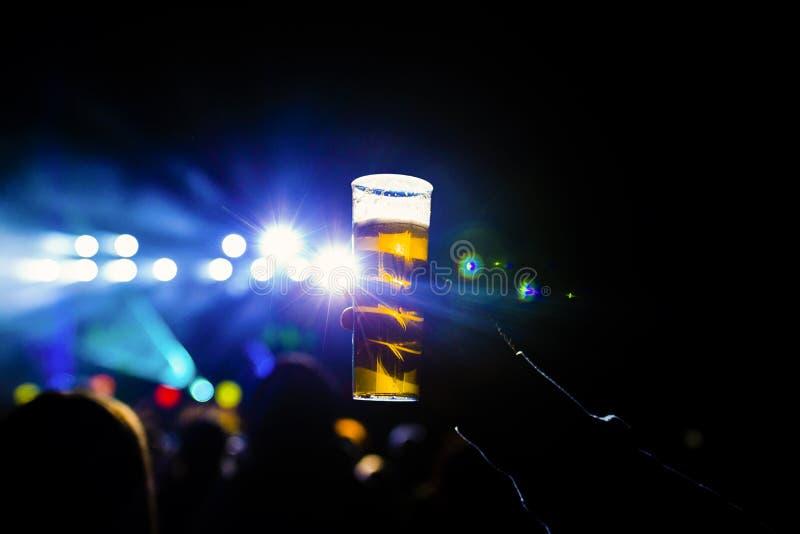 Uomo che tiene vetro di birra in un concerto di notte Fondo irriconoscibile della folla Indicatori luminosi blu immagine stock libera da diritti