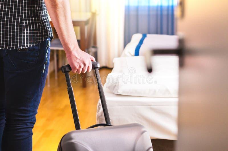 Uomo che tira valigia e che entra in camera di albergo immagine stock