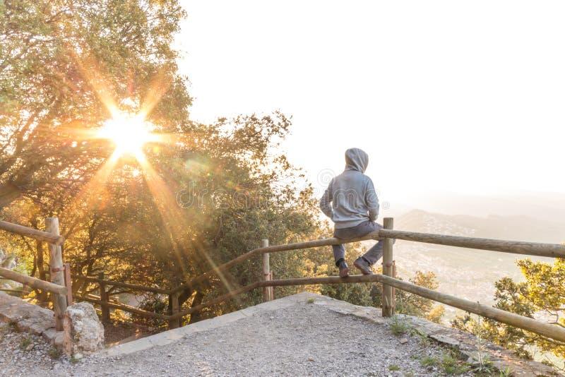 Uomo che trascura bello paesaggio sul banco della montagna immagine stock