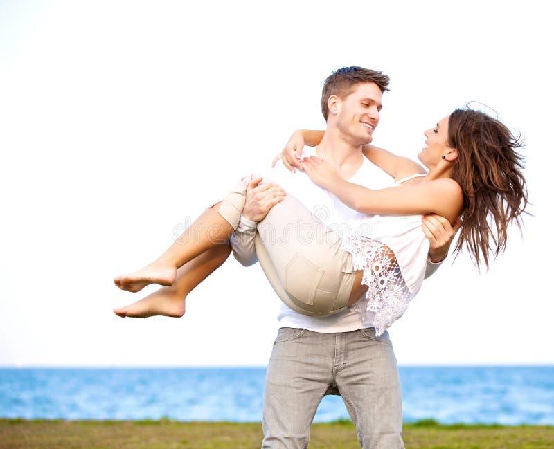 Uomo che trasporta la sua amica in una spiaggia ventosa immagini stock libere da diritti