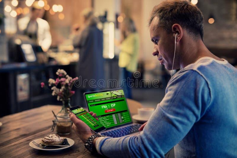 Uomo che usando gli sport online che scommettono i servizi sul telefono e sul computer portatile fotografia stock