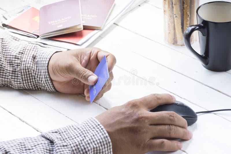 Uomo che usando la carta di credito per il pagamento che compera online intorno al viaggio ed al viaggio fotografia stock