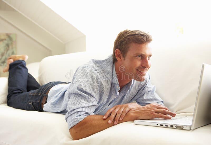 Uomo che usando seduta di distensione del computer portatile sul sofà nel paese fotografia stock