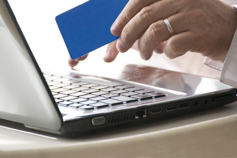 Uomo che usando un web di attività bancarie online che tiene una carta di credito e un computer portatile spazio vuoto della copi immagine stock libera da diritti