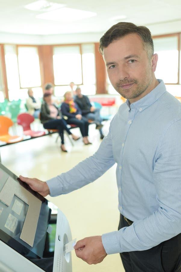 Uomo che utilizza chiosco elettronico nella sala di attesa dell'ospedale fotografia stock libera da diritti