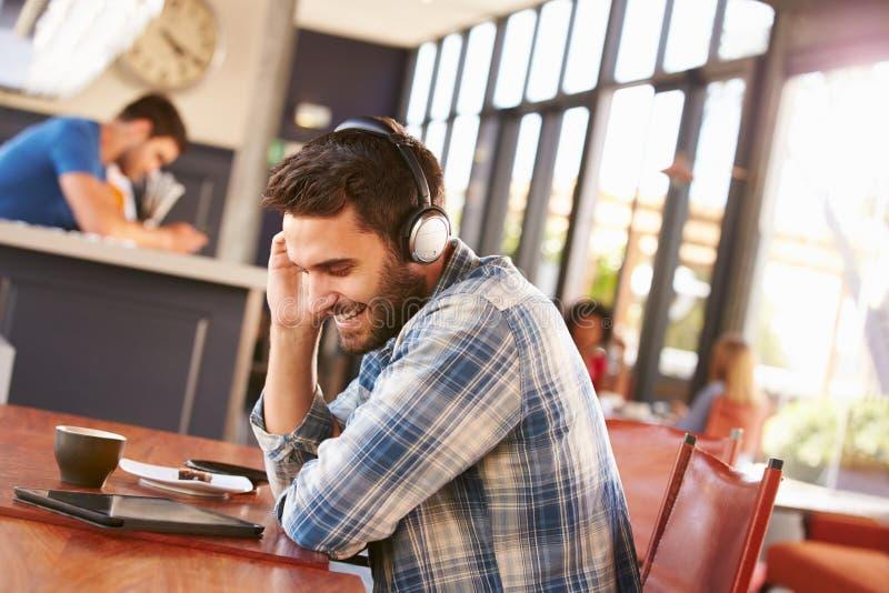 Uomo che utilizza compressa digitale in una caffetteria immagini stock