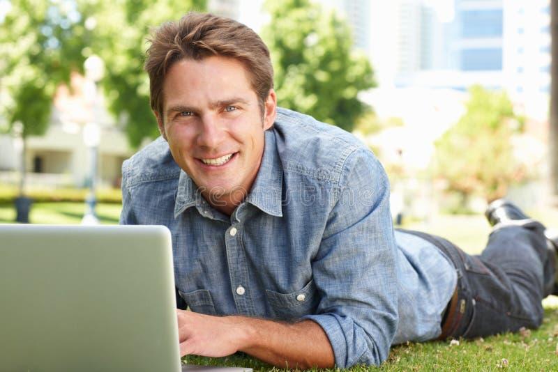 Uomo che utilizza computer portatile nella sosta della città immagine stock