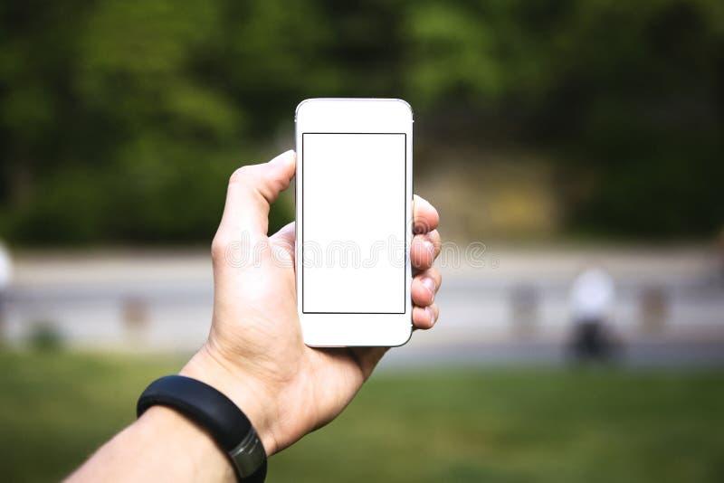 Uomo che utilizza telefono cellulare nel parco come macchina fotografica fotografia stock