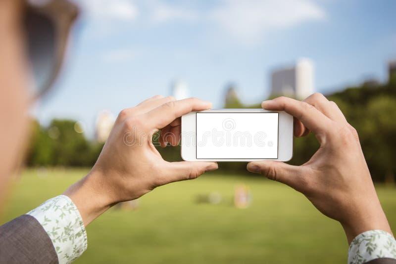 Uomo che utilizza telefono cellulare nel parco come macchina fotografica fotografie stock libere da diritti