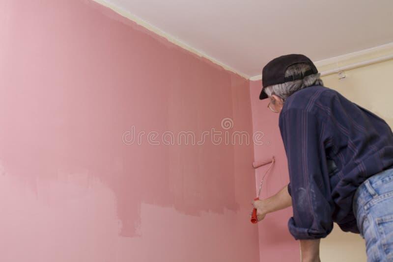 Uomo che vernicia una parete fotografia stock