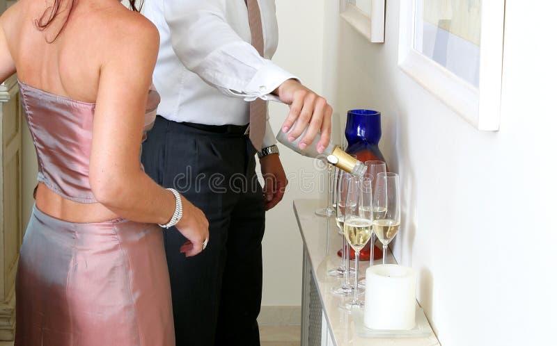 Uomo che versa Champagne ad un partito di pranzo fotografie stock libere da diritti