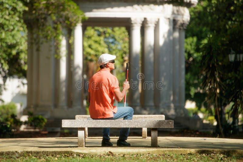Uomo cieco che si siede nel parco e nel riposo della città fotografia stock libera da diritti