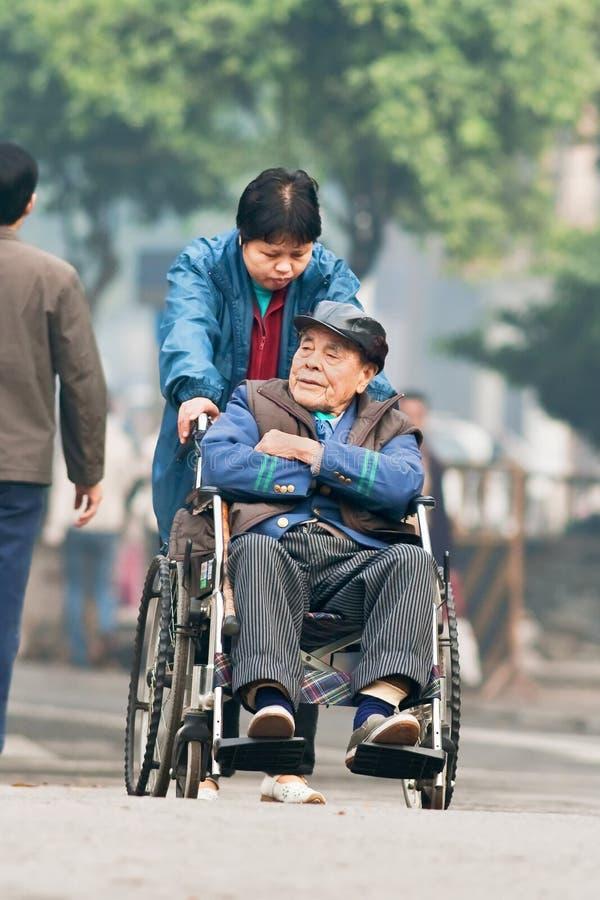 Uomo cinese anziano in una sedia a rotelle, Canton, Cina fotografie stock
