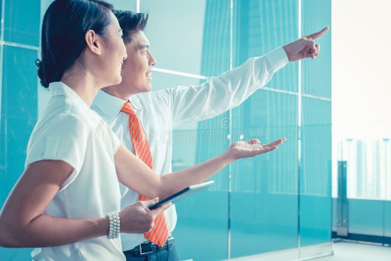 Uomo cinese di affari che spiega la sua visione o idea al collega fotografie stock