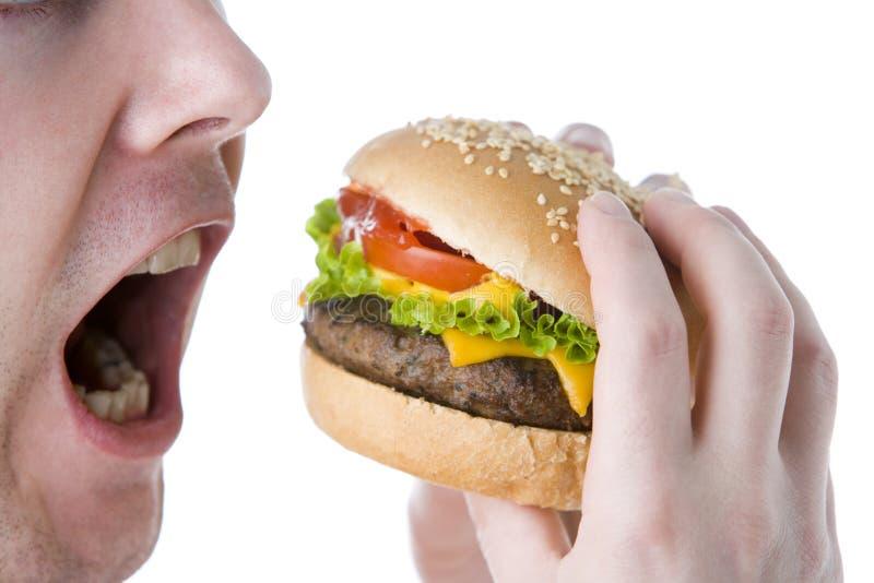 Uomo circa al morso in un cheeseburger fotografia stock