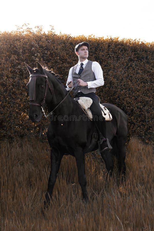 Uomo classico che monta un cavallo in un paesaggio autunnale fotografia stock