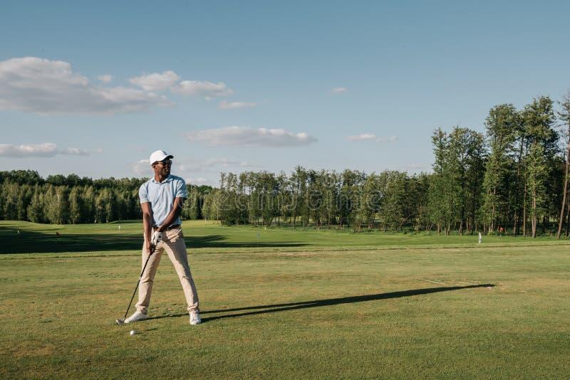 Uomo in club di golf della tenuta del cappuccio e palla colpire su prato inglese verde immagini stock libere da diritti