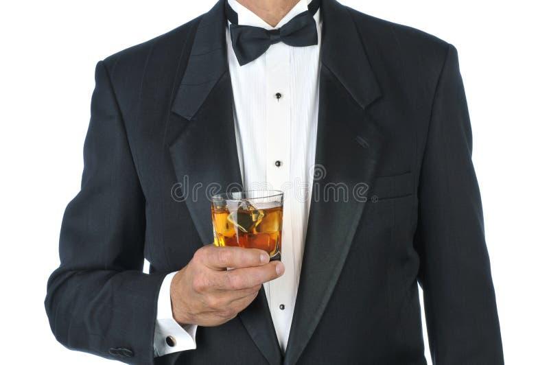 Uomo in cocktail della holding dello smoking fotografia stock