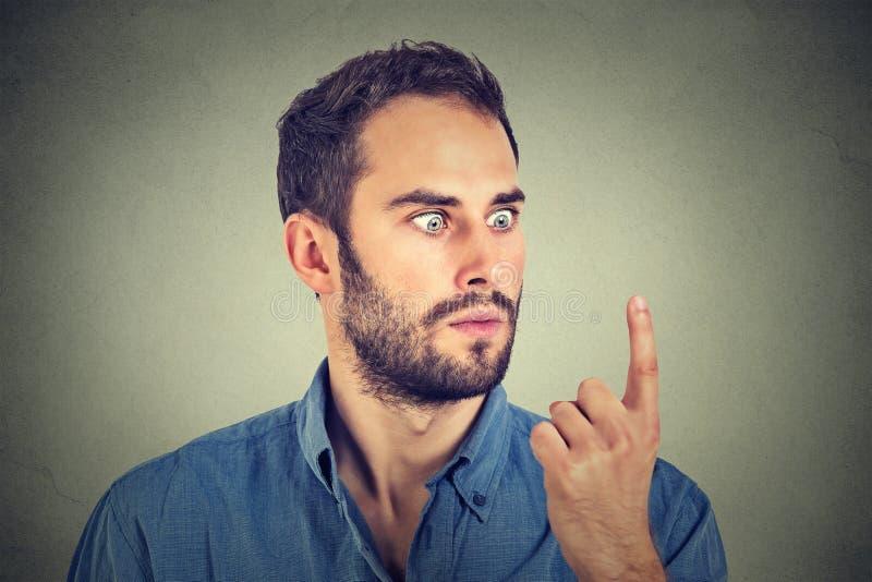 Uomo colpito che esamina il suo dito fotografie stock