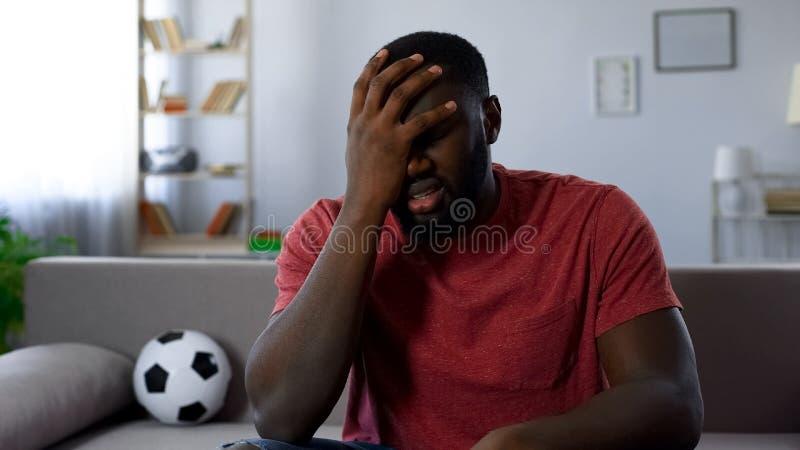 Uomo colpito dalla sconfitta della squadra di football americano in concorrenza, gruppo che lascia lega fotografie stock libere da diritti