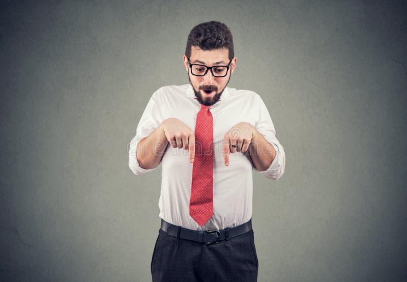 Uomo colpito di affari che guarda giù nell'incredulità, indicante con le dita al pavimento fotografia stock