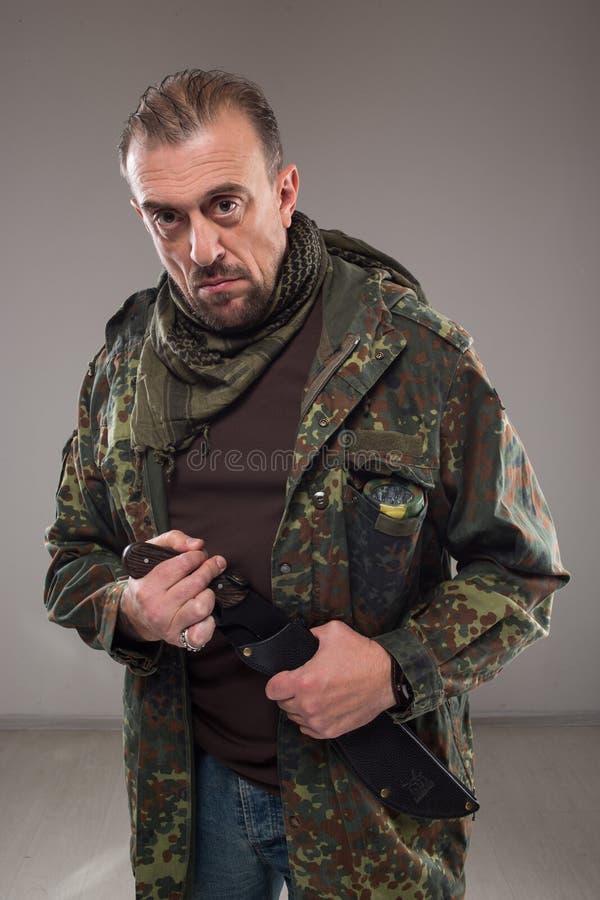 Uomo in coltello della tenuta dell'uniforme del soldato immagine stock libera da diritti