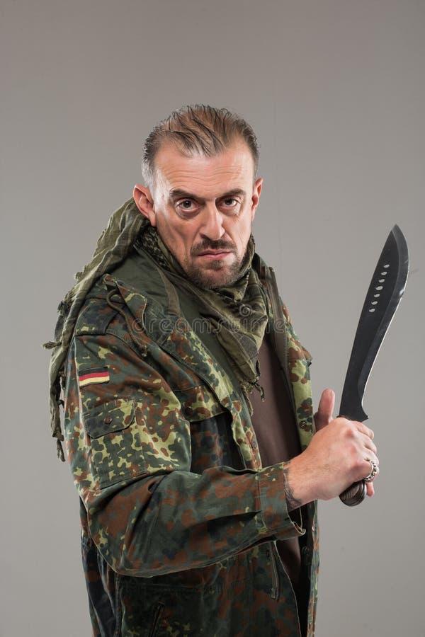 Uomo in coltello della tenuta dell'uniforme del soldato fotografia stock