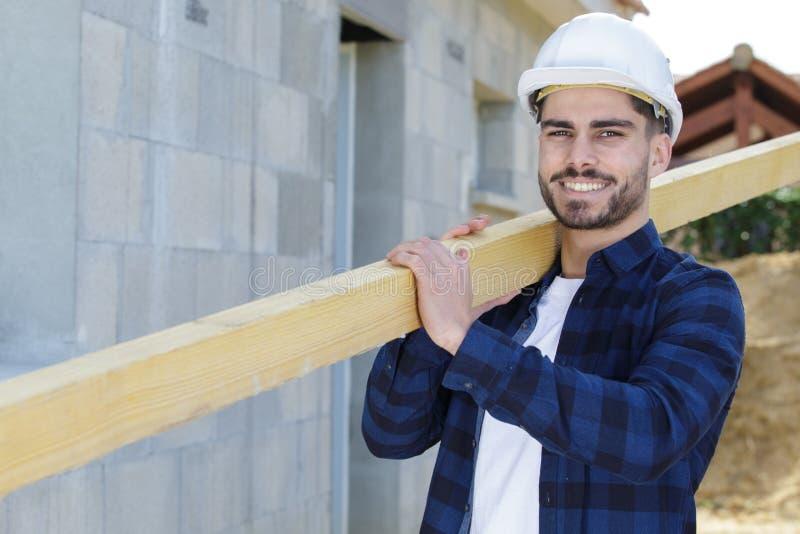 Uomo come il legno di trasporto e lavoro del costruttore fotografia stock